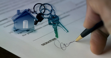 A person signing a lease to rent a house