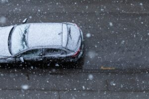 a black car being driven along a snowy road